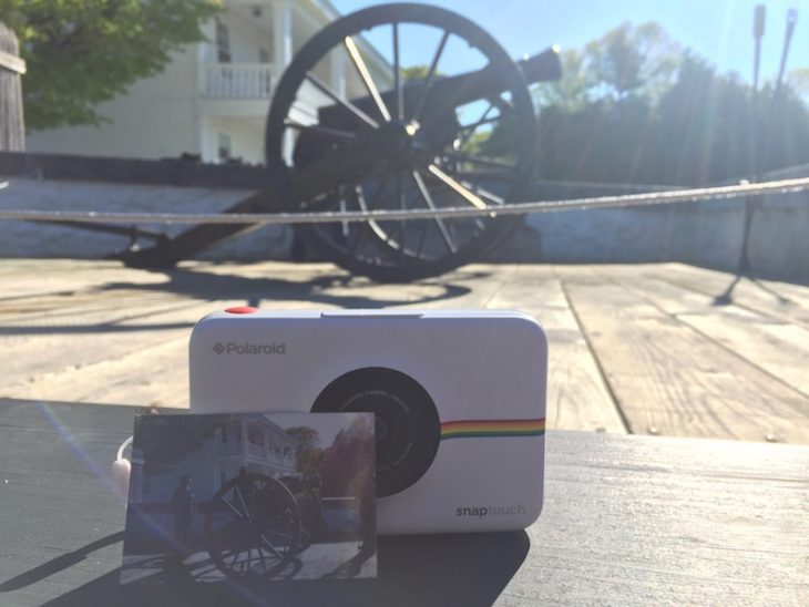 poloraid instant camera in front of cannon firing at fort mackinac