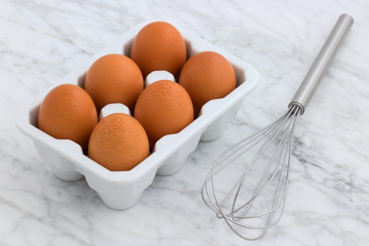 brown eggs in a white carton next to a metal whisk
