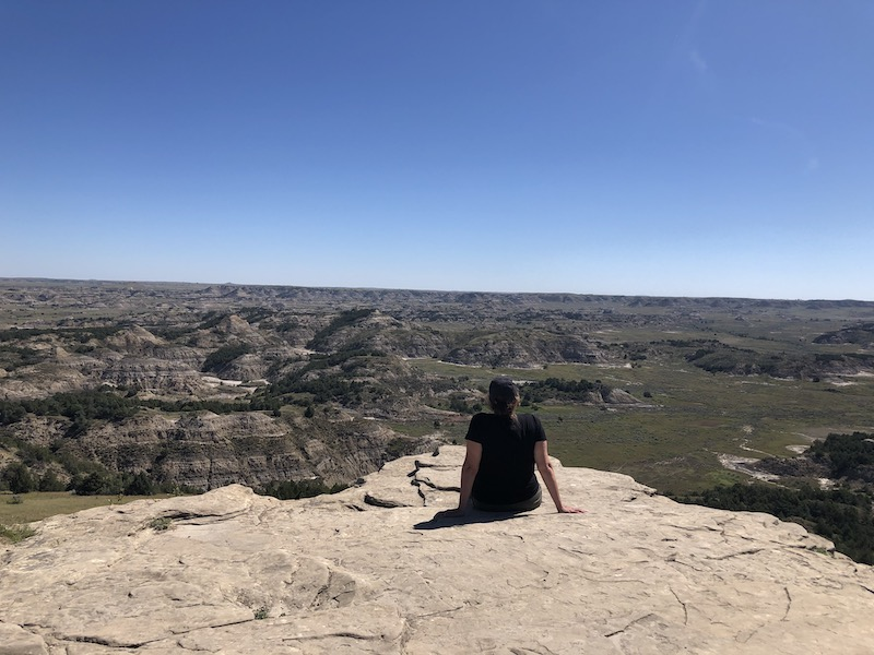 girl sitting on rock, back to camera, looking out over the landscape of theodore roosevelt national park