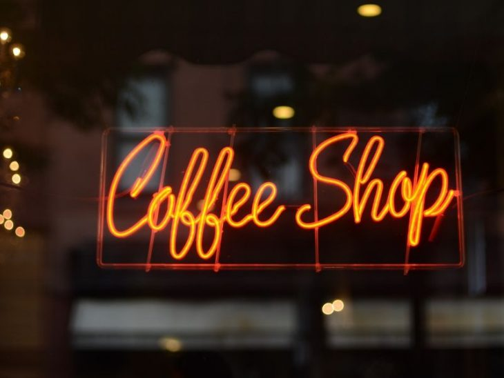 neon coffee shop sign in a script font with orange red color